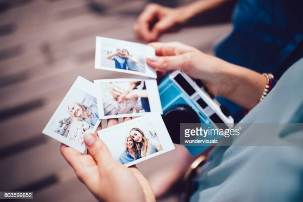 Young woman holding polaroid photos with mum on summer holidays
