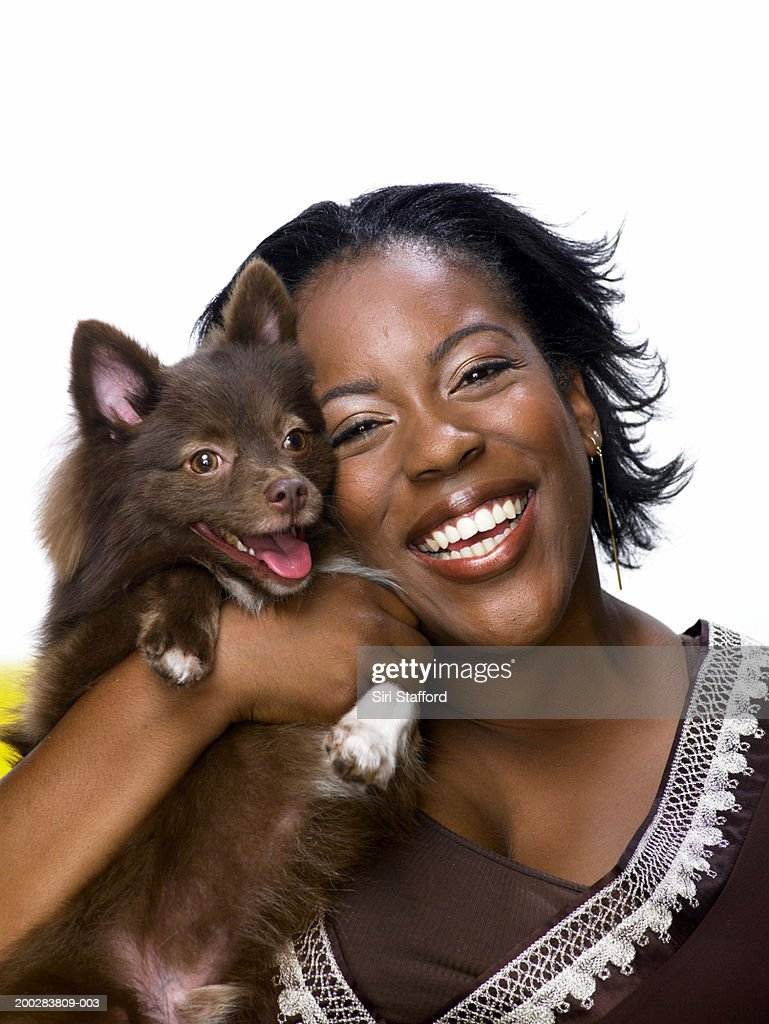 Young woman holding Pomeranian dog, smiling : Stock Photo