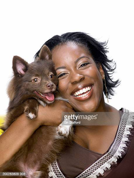 Young woman holding Pomeranian dog, smiling