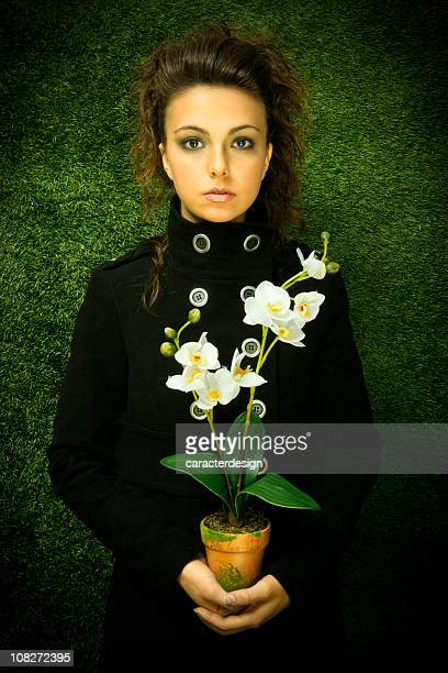 Young Woman Holding Pot of Orchid Flowers.