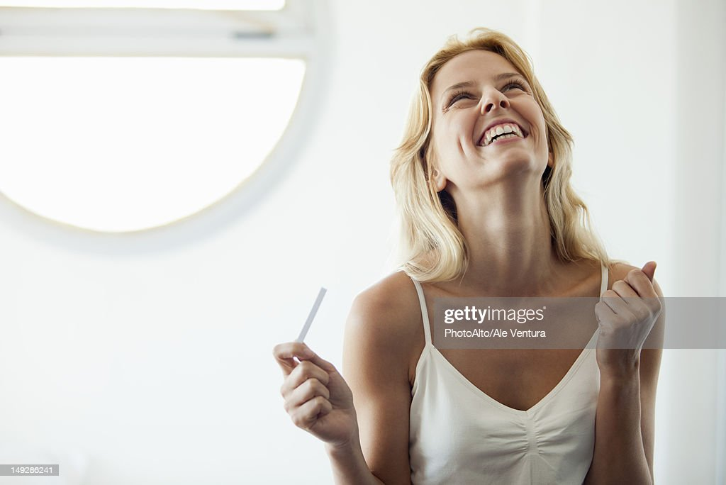 Young woman holding pregnancy test, laughing : Stock Photo