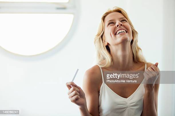 young woman holding pregnancy test, laughing - 頭をそらす ストックフォトと画像