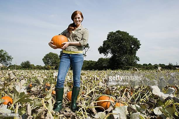 Young woman holding pumpkin