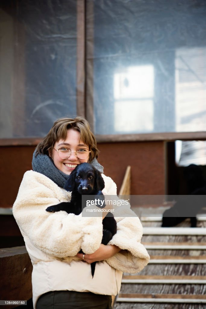Young woman holding purebred flat-coated retriever puppy. : Stock Photo