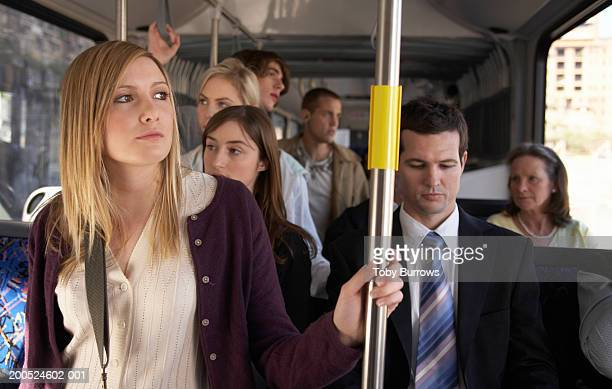 young woman holding railing on bus - bus stockfoto's en -beelden