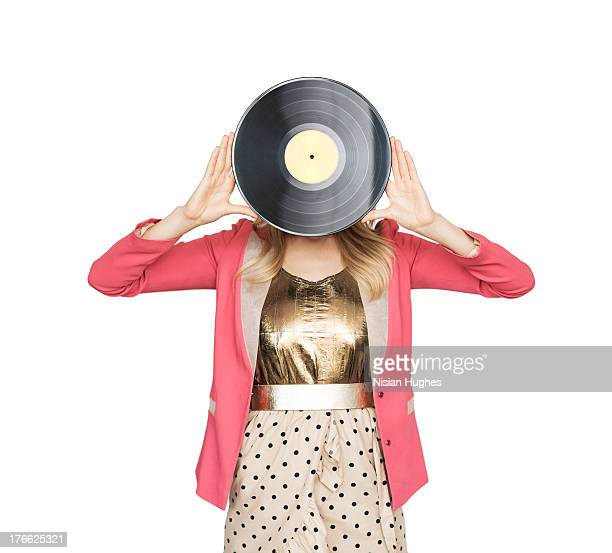 Young woman holding record in front of face