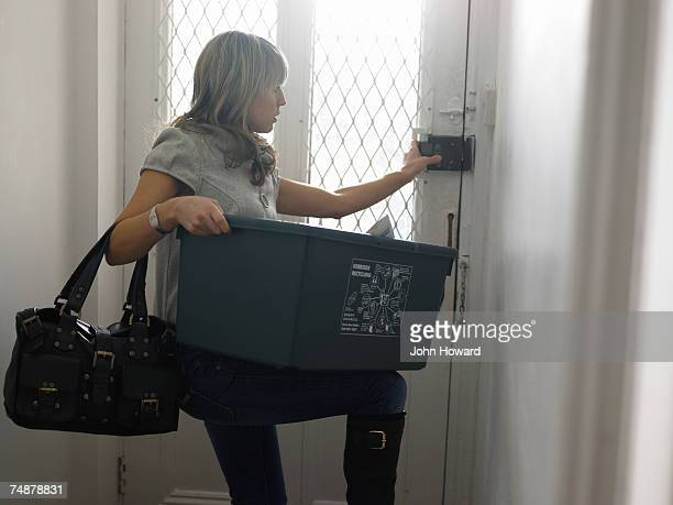 Young woman holding recycling box struggling to open front door