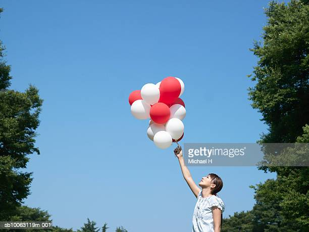 Young woman holding red and white balloons in park