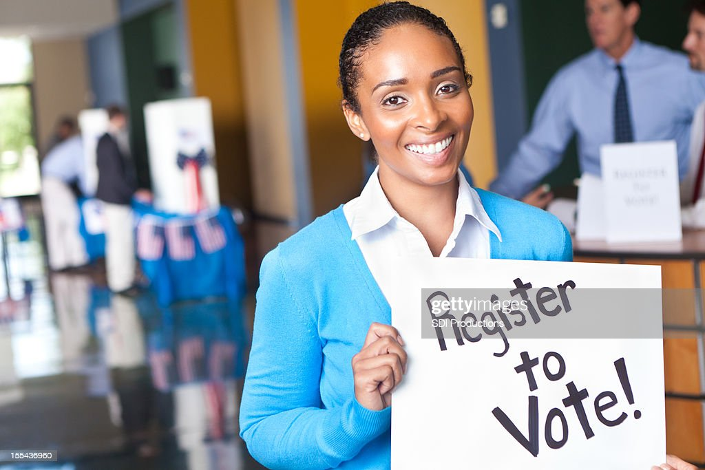 Young woman holding register to vote sign at voting center : Stock Photo