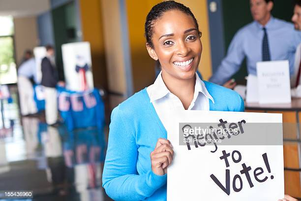 young woman holding register to vote sign at voting center - register stock photos and pictures