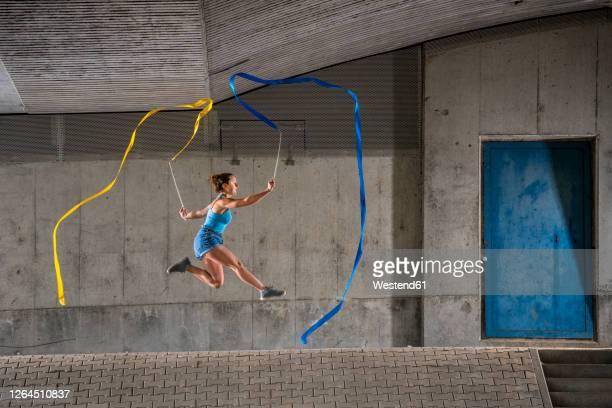 young woman holding ribbons practicing rhythmic gymnastics against concrete wall under bridge - gymnastique au sol photos et images de collection