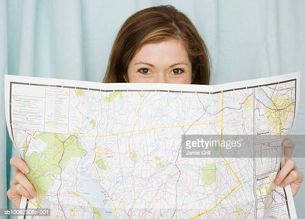 Young woman holding road map, portrait, close-up