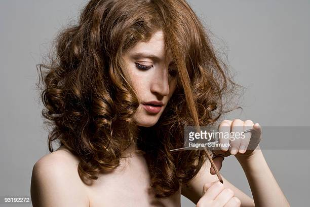 A young woman holding scissors and cutting her hair