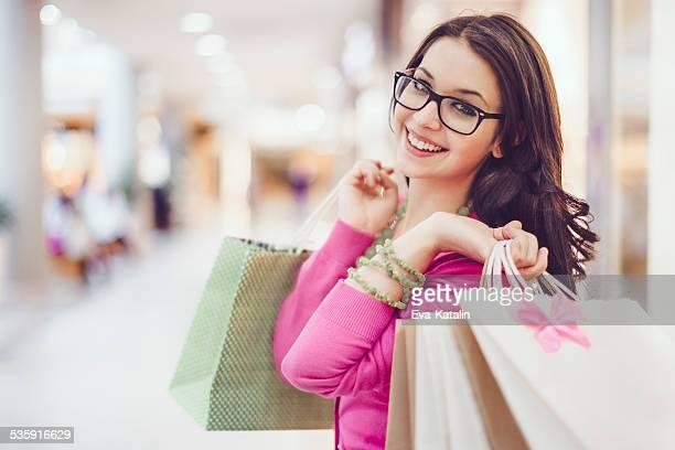 jovem mulher segurando sacolas de compras em um shopping - bolsa rosa - fotografias e filmes do acervo