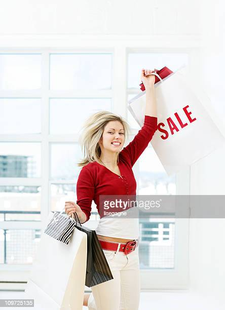 Young Woman Holding Shopping Bags Triumphantly