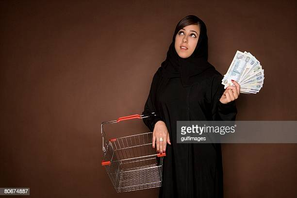 Young woman holding shopping cart and paper currency