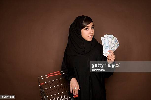 Young woman holding shopping cart and paper currency, portrait