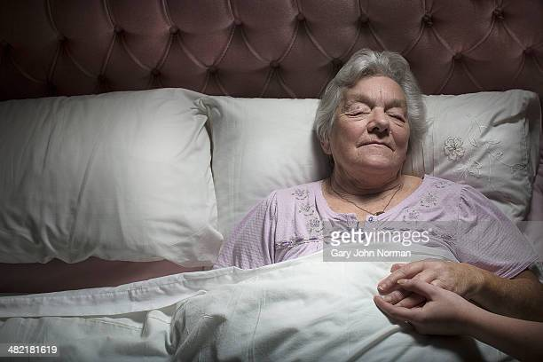 Young woman holding sleeping senior woman's hand