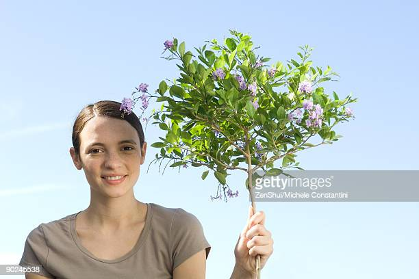 Young woman holding slender trunk of flowering tree, smiling at camera