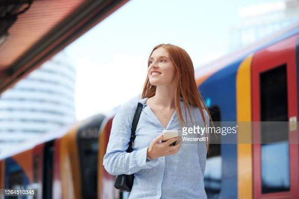 young woman holding smart phone at railroad station - bahnreisender stock-fotos und bilder