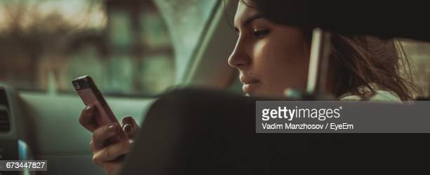 young woman holding smart phone in car - car photos stock pictures, royalty-free photos & images
