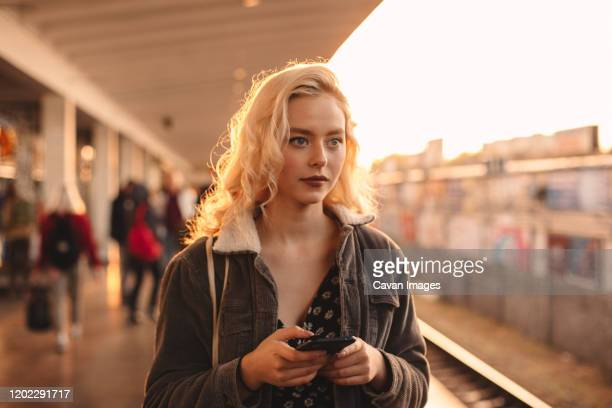young woman holding smart phone while waiting for train - 地下鉄のプラットホーム ストックフォトと画像