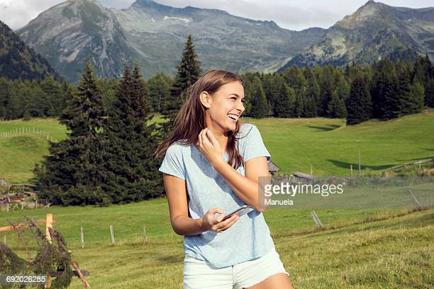 Young woman holding smartphone and laughing in Austrian Alps, Sattelbergalm, Tirol, Austria