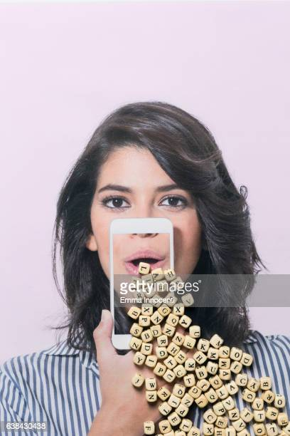 Young woman holding smartphone up to her mouth with letter falling out