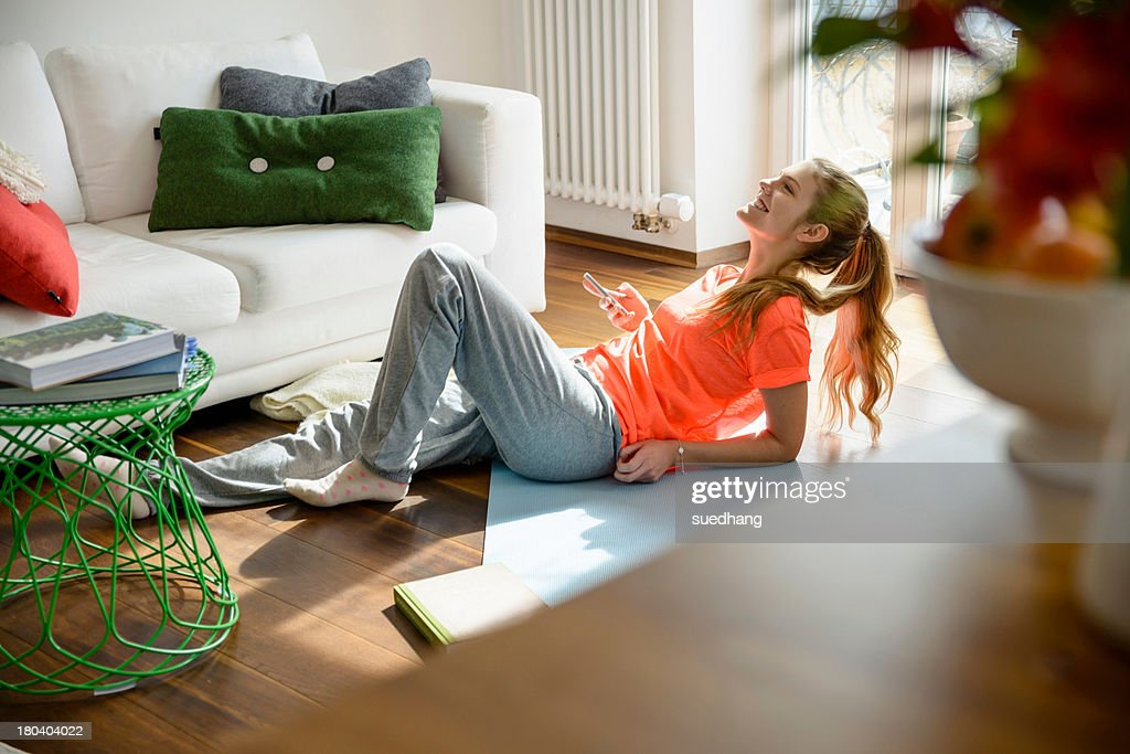 Young woman holding smartphone whilst lounging on floor : Stock Photo