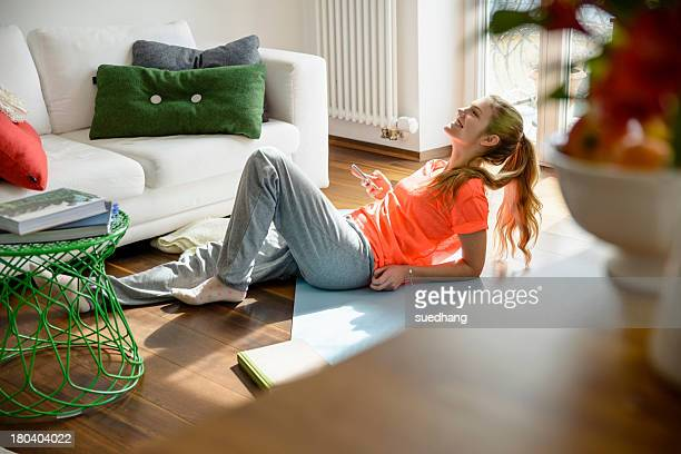 young woman holding smartphone whilst lounging on floor - tracksuit bottoms stock pictures, royalty-free photos & images