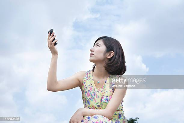 Young woman holding smartphone,sky background