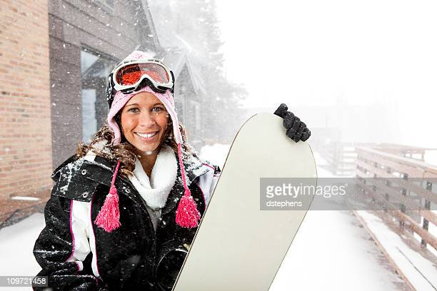 Young woman holding snowboard in snowstorm