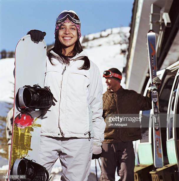 young woman holding snowboard, smiling, portrait - ski pants stock pictures, royalty-free photos & images
