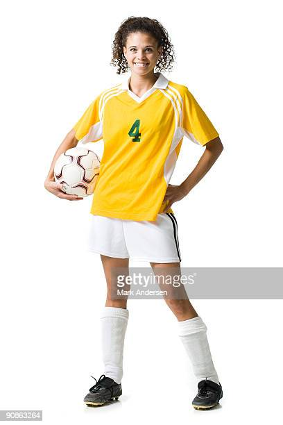 Young woman holding soccer ball smiling