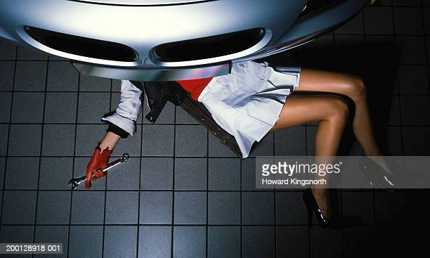 young woman holding spanner under car, low section, overhead view - under skirt stock photos and pictures