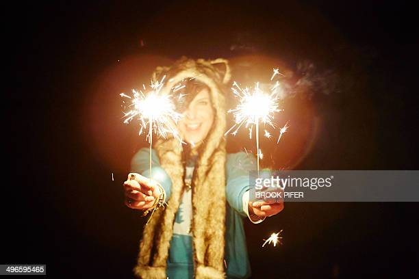 Young woman holding sparklers