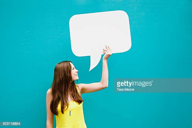 young woman holding speech bubble in front of blue wall - speech bubble stock pictures, royalty-free photos & images