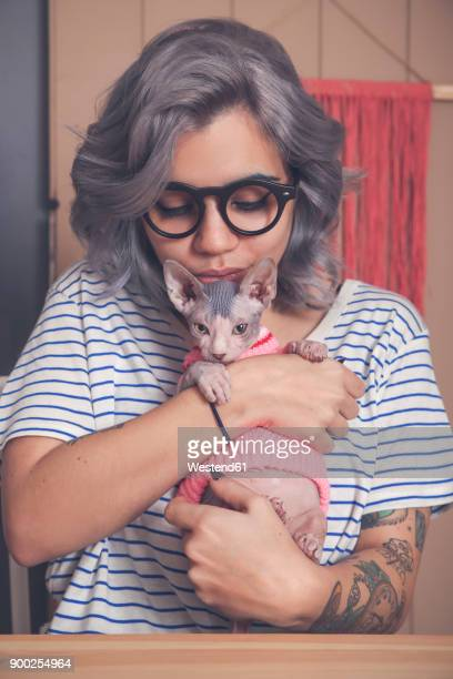 Young woman holding Sphynx cat wearing pullover
