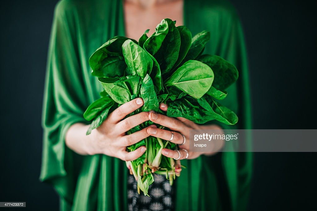 Young woman holding spinach leafs salad : Stockfoto