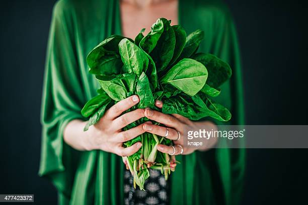 young woman holding spinach leafs salad - freshness stockfoto's en -beelden