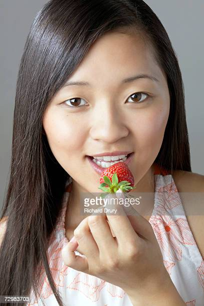 Young woman holding strawberry to mouth, portrait
