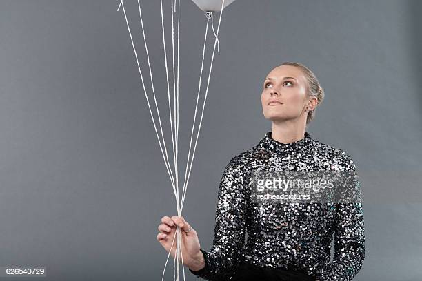 Young woman holding strings tied to balloon, grey background