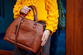 Young woman holding stylish handbag and wearing yellow sweater. Spring female clothes and accessories. Fashion