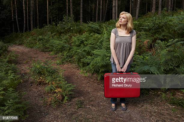Young woman holding suitcase on forest path