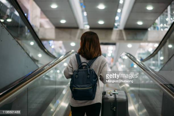 young woman holding suitcase or baggage with backpack in the international airport. - cambio horario fotografías e imágenes de stock