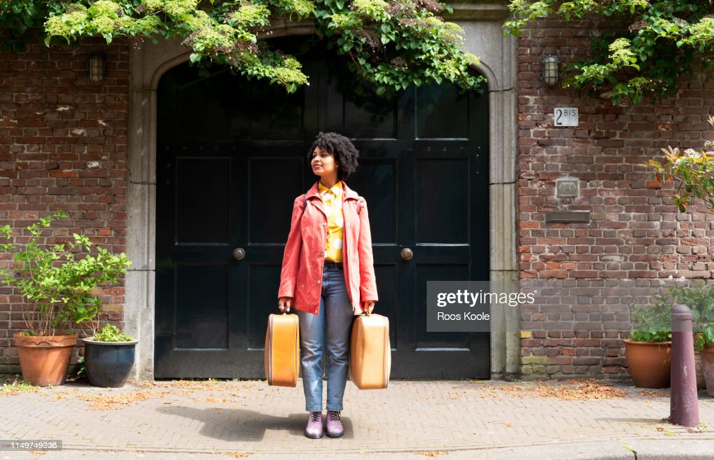 A young woman holding suitcases. : Photo