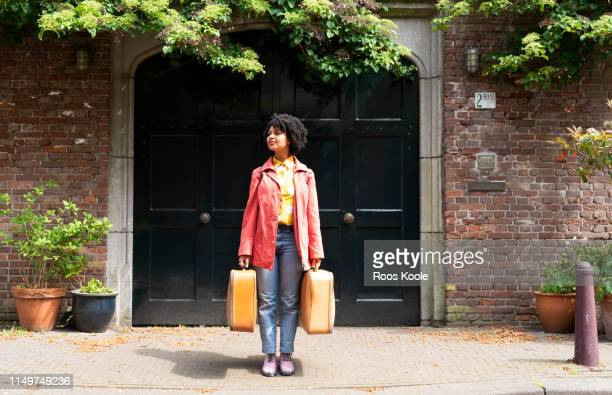 a young woman holding suitcases. - leaving photos et images de collection