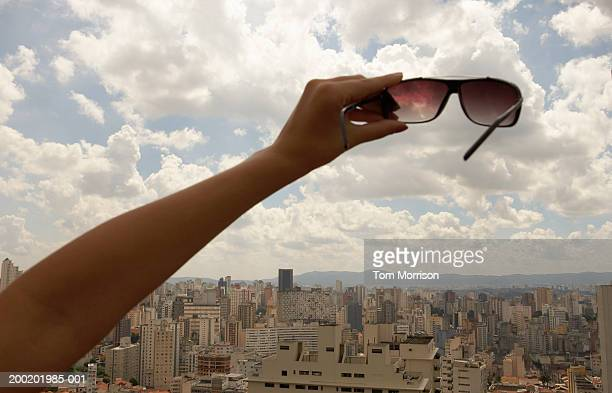 Young woman holding sunglasses out to sky, close-up