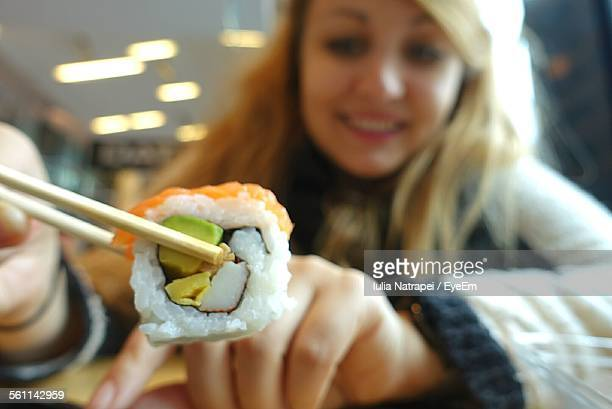 Young Woman Holding Sushi With Chopsticks