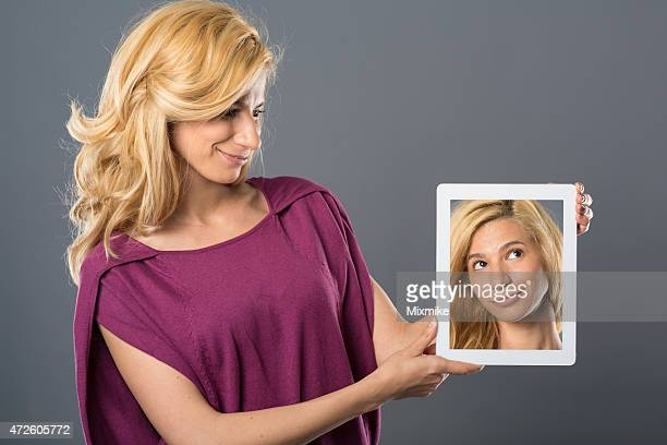 Young woman holding tablet with her photo